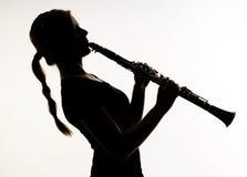 O músico fêmea na silhueta pratica a técnica dos sopros no Cl Imagens de Stock