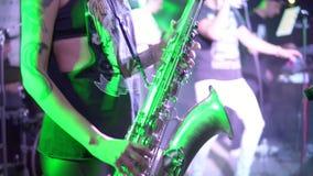 O músico irreconhecível está jogando no saxofone no concerto Close-up nos dedos que pressionam as chaves do instrumento