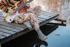 O músico joga a guitarra que senta-se na ponte no autum fotografia de stock