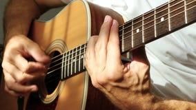 O músico joga um ritmo rápido em uma guitarra acústica amarela, guardando as cordas na barra video estoque
