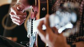 O músico masculino joga a guitarra, mãos perto acima vídeos de arquivo