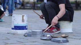 O músico mostra fora suas habilidades da percussão em uma cubeta e em pratos na rua video estoque