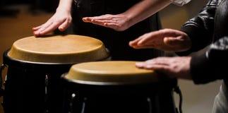 O m?sico joga os bongos Feche acima da m?o do m?sico que joga cilindros de bongos Afro Cuba, rum, baterista, dedos, mão foto de stock royalty free