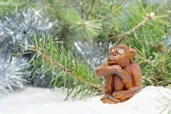 O macaco alegre sonhador da cerâmica da argila senta-se na neve perto da árvore Imagem de Stock Royalty Free