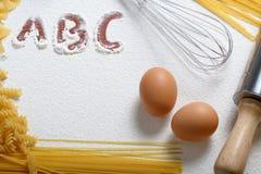 O macarrão Uncooked, whisk e ovos Fotografia de Stock Royalty Free