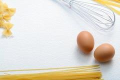 O macarrão Uncooked, whisk e ovos na farinha de trigo Fotos de Stock Royalty Free