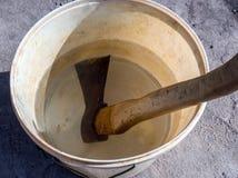 O machado velho encontra-se em uma cubeta da água Foto de Stock Royalty Free