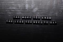 O mais que você conhece, menos você precisa de dizer em blocos de madeira Conceito da educa??o, da motiva??o e da inspira??o ilustração royalty free