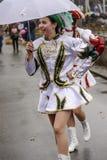 O majorette novo sorri sob o guarda-chuva branco na parada de carnaval, Fotografia de Stock Royalty Free