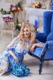 O makiyad profissional e o cabelo do retrato bonito da mulher do modelo da menina em uma flor vestem-se em um fundo floral, tom b Imagem de Stock Royalty Free