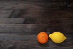 O mandarino alaranjado e limão amarelo em um fundo de madeira rústico escuro Imagens de Stock Royalty Free