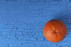 O mandarino alaranjado em um fundo azul com craquelures Fotos de Stock