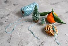 O mandarino com folhas e luzes, laranja da tangerina em decorações do ano de Gray Table Background Christmas New fotos de stock