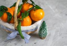 O mandarino de madeira da cesta com folhas e luzes, laranja da tangerina em decorações do ano de Gray Table Background Christmas  fotos de stock royalty free