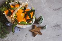 O mandarino de madeira da cesta com folhas e luzes, laranja da tangerina em decorações do ano de Gray Table Background Christmas  fotos de stock