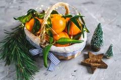 O mandarino de madeira da cesta com folhas e luzes, laranja da tangerina em decorações do ano de Gray Table Background Christmas  foto de stock
