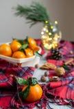 O mandarino de madeira da cesta com folhas e luzes, laranja da tangerina em decorações do ano de Gray Table Background Christmas  foto de stock royalty free