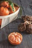 O mandarino e uma cesta de vime das tangerinas ao lado de um grupo de figos secados imagem de stock royalty free