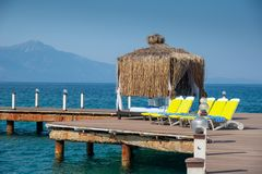 O mandril de madeira está em uma praia ensolarada Céu azul e montanha no fundo Férias e feriado no conceito da praia fotos de stock