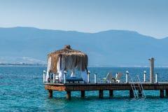 O mandril de madeira está em uma praia ensolarada Céu azul e montanha no fundo Férias e feriado no conceito da praia foto de stock
