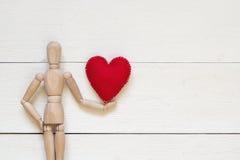 O manequim de madeira clássico guarda o coração vermelho para o dia do ` s do Valentim imagens de stock