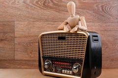 O manequim de madeira está na pose relaxado atrás do receptor de rádio que põe suas mãos sobre ele Fundo de madeira fotografia de stock royalty free