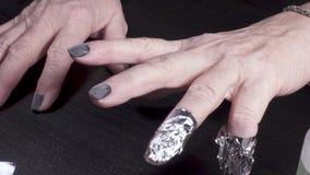O manicuro envolve o dedo na folha vídeos de arquivo