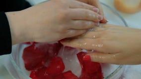 O manicuro enxágua as mãos fêmeas na água com pétalas vídeos de arquivo