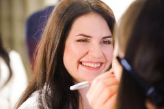 O maquilhador aplica o batom Face bonita da mulher Composição perfeita fotos de stock