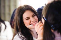 O maquilhador aplica o batom Face bonita da mulher Composição perfeita foto de stock royalty free