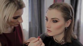 O maquilhador aplica a composição profissional a uma moça bonita Novo conceito na composição video estoque