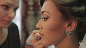 O maquilhador aplica a composição a uma noiva atrativa video estoque