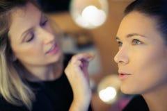 O maquilhador aplica o skintone Fotografia de Stock