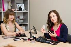 O maquilhador deixa seu cliente do cartão Foto de Stock