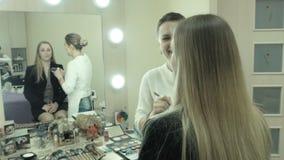 O maquilhador diz como ela que aplica cosméticos filme