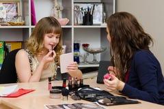 O maquilhador diz a menina como o batom Foto de Stock