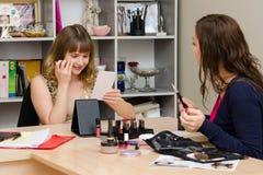 O maquilhador diz o cliente para consultar Imagens de Stock