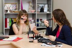 O maquilhador diz a uma menina como aplicar o pó Imagem de Stock Royalty Free