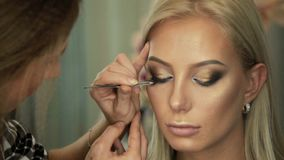 O maquilhador do bar da beleza cola as pestanas aos olhos louros video estoque