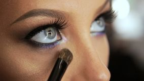 O maquilhador do bar da beleza induz as pestanas com um lápis louro do olho do escova-rímel filme