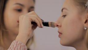 O maquilhador e o barbeiro profissionais criam uma imagem bonita para uma moça bonita vídeos de arquivo
