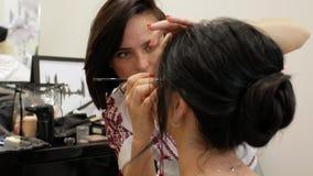 O maquilhador faz a composição de uma menina moreno bonita estilista que trabalha na imagem do modelo o maquilhador tira os olhos video estoque