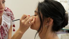 O maquilhador faz a composição de uma menina moreno bonita estilista que trabalha na imagem do modelo o maquilhador tira os olhos vídeos de arquivo