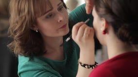 O maquilhador faz a composição do olho dos modelos filme