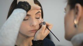 O maquilhador faz a composição do olho dos modelos video estoque