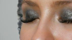 O maquilhador faz a modelos os olhos fumarentos com a ajuda da sombra cinzenta da escova especial, os olhos e as pestanas do fim  video estoque