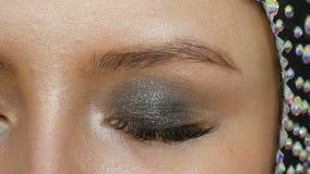O maquilhador faz a modelos os olhos fumarentos com a ajuda da sombra cinzenta da escova especial, os olhos e as pestanas do fim  vídeos de arquivo
