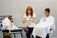 O maquilhador internacional do mestre da perfumaria de Intercharm Autumn Moscow XXI e da exposição dos cosméticos aplica a fêmea  Fotos de Stock