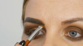 O maquilhador mestre profissional aplica a sombra bege com a escova especial no olho modelo no fim do salão de beleza acima da vi filme