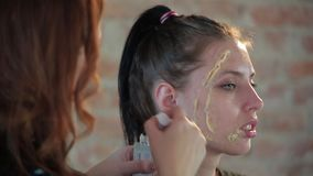 O maquilhador profissional da mulher do close-up aplica a cera na cara da menina bonito nova para a composi??o pl?stica para o ci filme